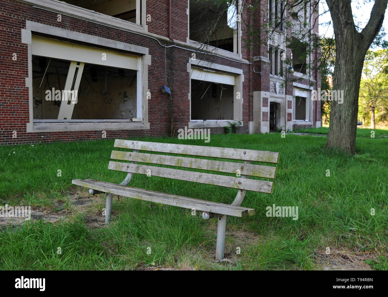 A wooden bench sits in front of an abandoned public school in Detroit, Michigan. All of the building's windows and doors have been broken or removed. - Stock Image