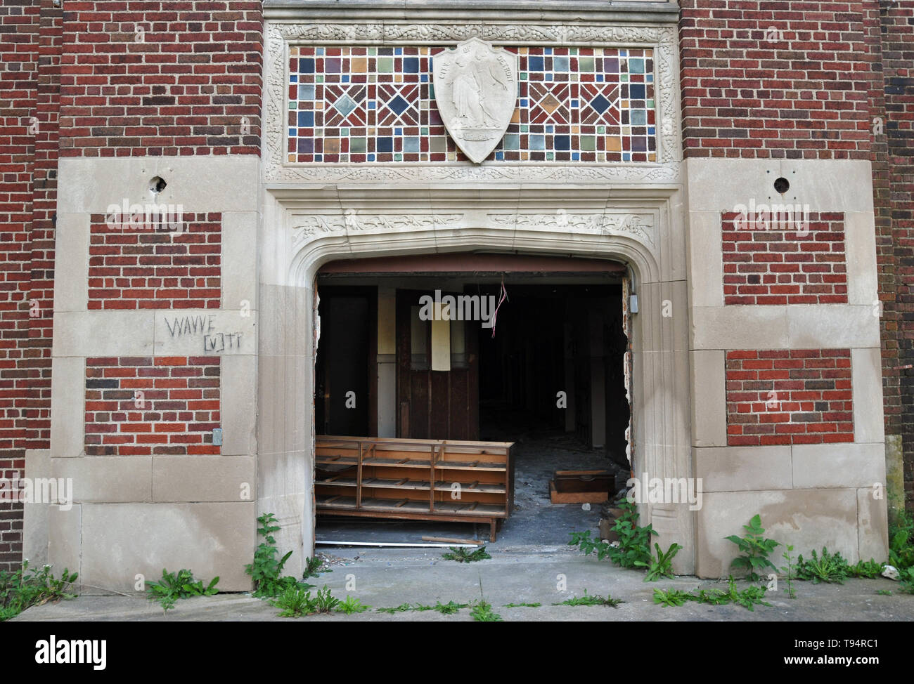 Detail of the gaping front entrance to an abandoned public school in Detroit, Michigan. All of the building's windows and doors are broken or missing. - Stock Image
