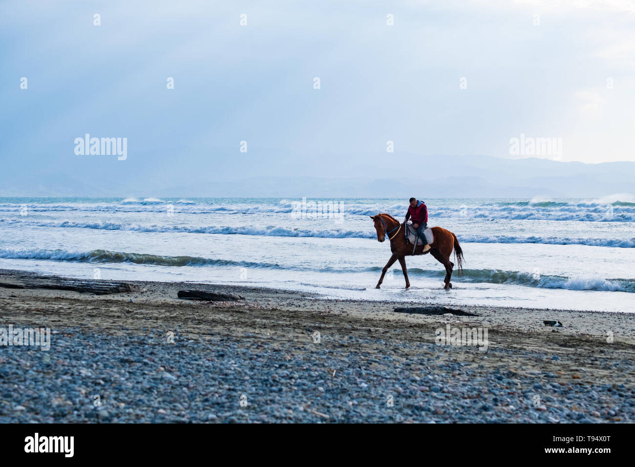 Ayia Eirini, Cyprus - 24 March, 2019: Man riding on a brown galloping horse in the sea waters of Ayia Erini beach in Cyprus against a rough sea - Stock Image