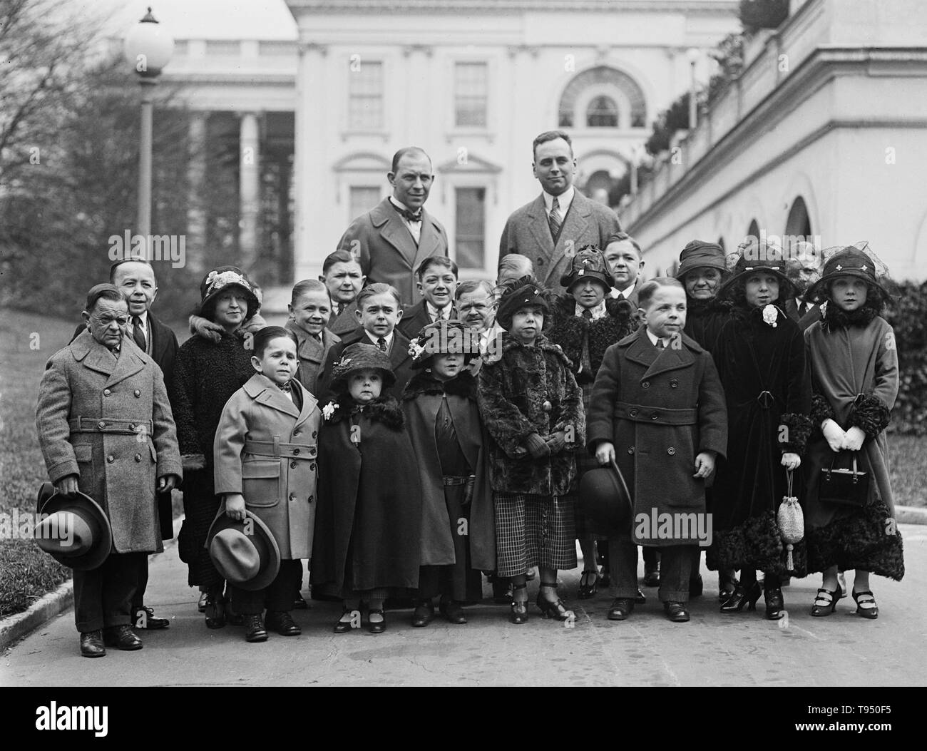 Entitled: 'The entire company of the tiny men and women who compose the famous singer midgets were received by President Coolidge. Roland Robbins, manager of B.F. Keith's Theatre accompanied these little people to the White House. They have appeared in almost every country in the world.' Singer's Midgets were a popular vaudeville group in the first half of the 20th century. Leopold von Singer (May 3, 1877 - March 5, 1951) formed Singer's Midgets in 1912-13, and built the Liliputstadt, a 'midget city' at the 'Venice in Vienna' amusement park, where they performed. The Liliputstadt was a major s - Stock Image