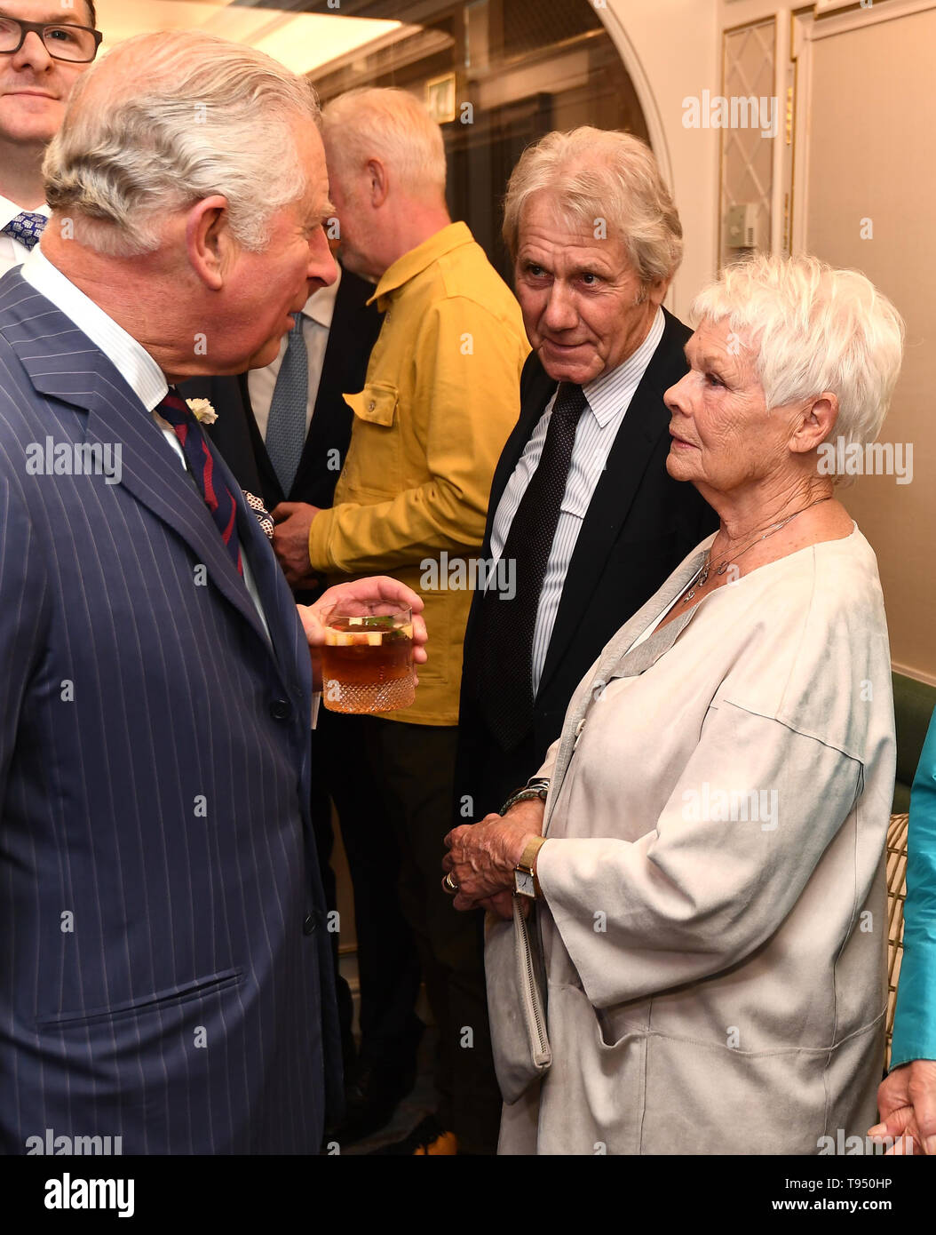 The Prince of Wales talks with Dame Judi Dench and her partner David Mills, at the annual Fortnum & Mason Food and Drink Awards at Fortnum & Mason, central London. - Stock Image