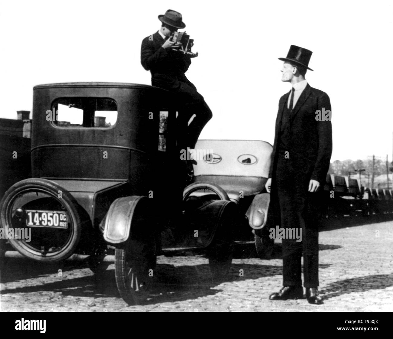 """Entitled: """"Photographer seated on top of car photographing tall man in top hat."""" Gigantism, also known as giantism, is a condition characterized by excessive growth and height significantly above average. In humans, this condition is caused by over-production of growth hormone in childhood resulting in people between 7 feet and 9 feet in height. National Photo Company, 1922. Stock Photo"""
