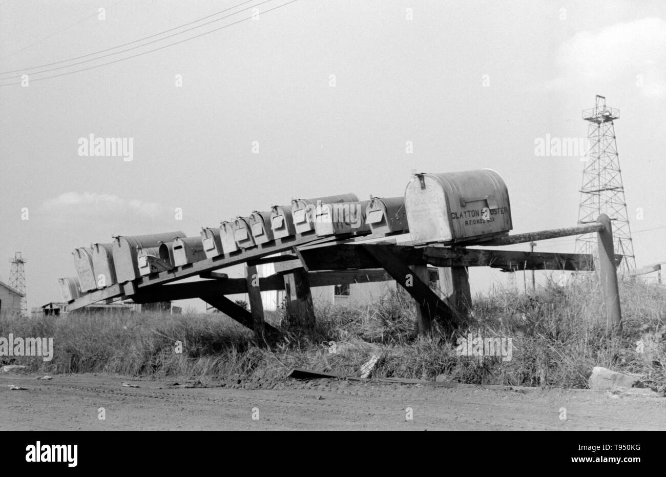 """Entitled: """"Mail boxes, Seminole oil field, Oklahoma."""" Before the introduction of rural free delivery (RFD) by the Post Office in 1896, many rural residents had no access to the mail unless they collected it at a post office located many miles from their homes or hired a private express company to deliver it. For this reason, mailboxes did not become popular in rural America until curbside RFD mail delivery by the Post Office was an established service. Stock Photo"""