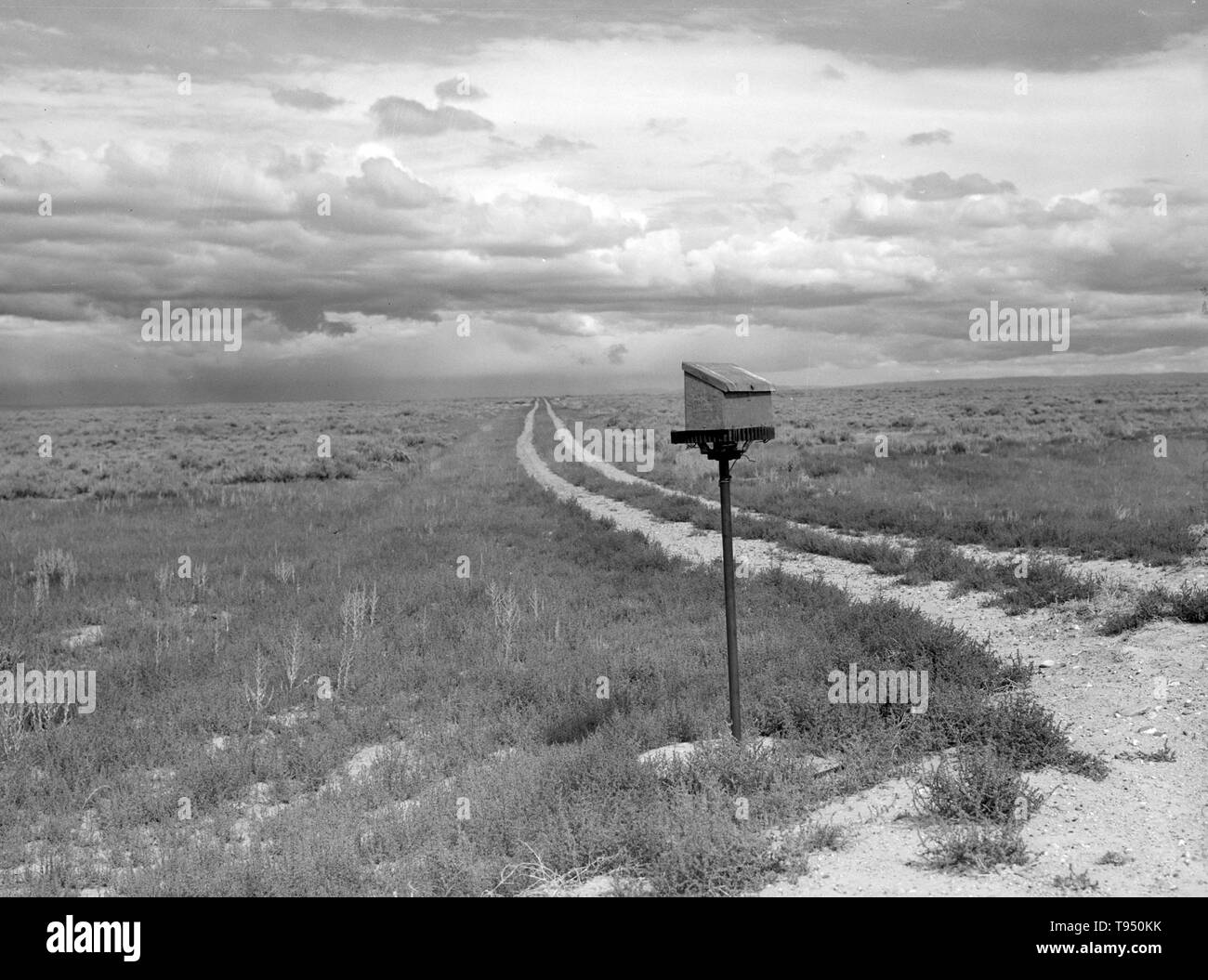"""Entitled: """"Ranch mailbox near Farson, Wyoming."""" Before the introduction of rural free delivery (RFD) by the Post Office in 1896, many rural residents had no access to the mail unless they collected it at a post office located many miles from their homes or hired a private express company to deliver it. For this reason, mailboxes did not become popular in rural America until curbside RFD mail delivery by the Post Office was an established service. Stock Photo"""