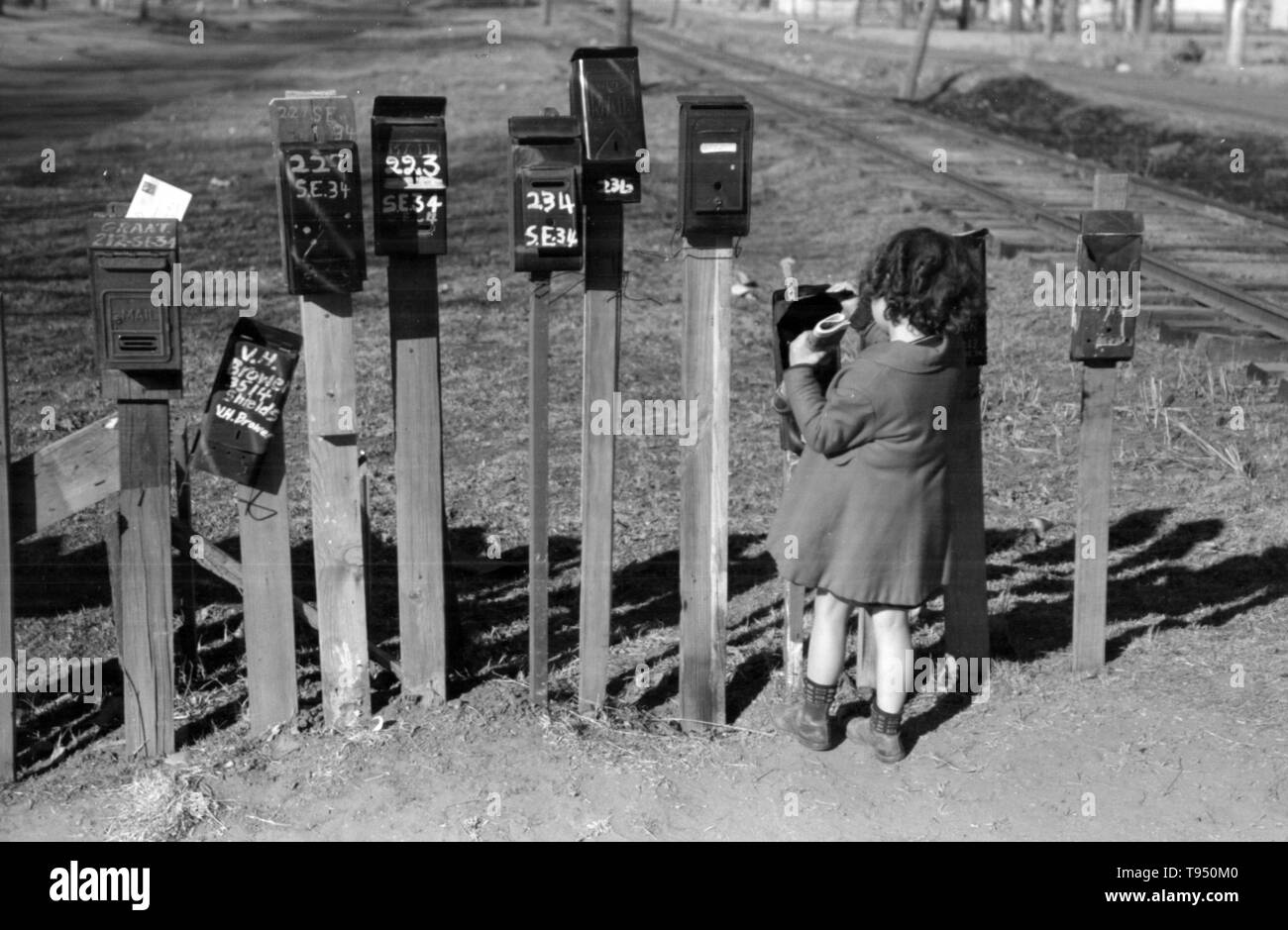 """Entitled: """"Little girl getting the mail from box, suburb of Oklahoma City, Oklahoma."""" Before the introduction of rural free delivery (RFD) by the Post Office in 1896, many rural residents had no access to the mail unless they collected it at a post office located many miles from their homes or hired a private express company to deliver it. For this reason, mailboxes did not become popular in rural America until curbside RFD mail delivery by the Post Office was an established service. Stock Photo"""