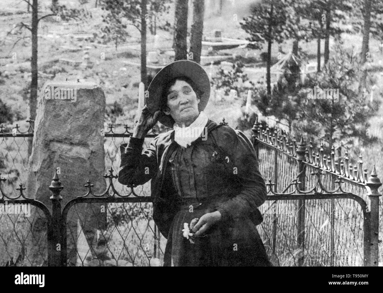 Calamity Jane, standing by the grave of Wild Bill Hickok, photogrpahed by J.A. Kumpf, 1903. Martha Jane Canary (May 1, 1852 - August 1, 1903), better known as Calamity Jane, was an American frontierswoman and professional scout. She received little to no formal education and was illiterate. She worked as a dishwasher, a cook, a waitress, a dance-hall girl, a nurse, and an ox team driver. In 1874, she found work as a scout at Fort Russell. In 1876, she settled in the area of Deadwood and became friendly with Wild Bill Hickok and Charlie Utter. After Hickok's death she continued living in the De - Stock Image