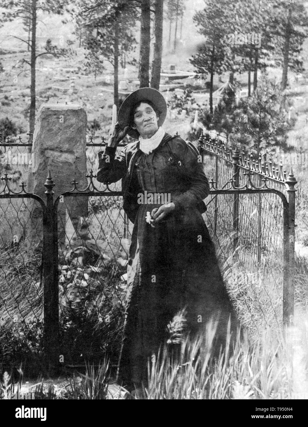 Calamity Jane, standing by the grave of Wild Bill Hickok, photogrpahed by J.A. Kumpf, 1903. Martha Jane Canary (May 1, 1852 - August 1, 1903), better known as Calamity Jane, was an American frontierswoman and professional scout. She received little to no formal education and was illiterate. She worked as a dishwasher, a cook, a waitress, a dance-hall girl, a nurse, and an ox team driver. In 1874, she found work as a scout at Fort Russell. In 1876, she settled in the area of Deadwood and became friendly with Wild Bill Hickok and Charlie Utter. In 1881, she bought a ranch in Montana, along the Y - Stock Image