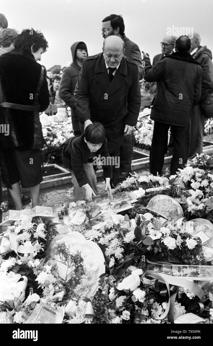 Seven-year-old Gerald Sands - who lives in England with his mother - places a wreath on the grave of his father Bobby Sands during the burial service at Milltown cemetery, Belfast. - Stock Image