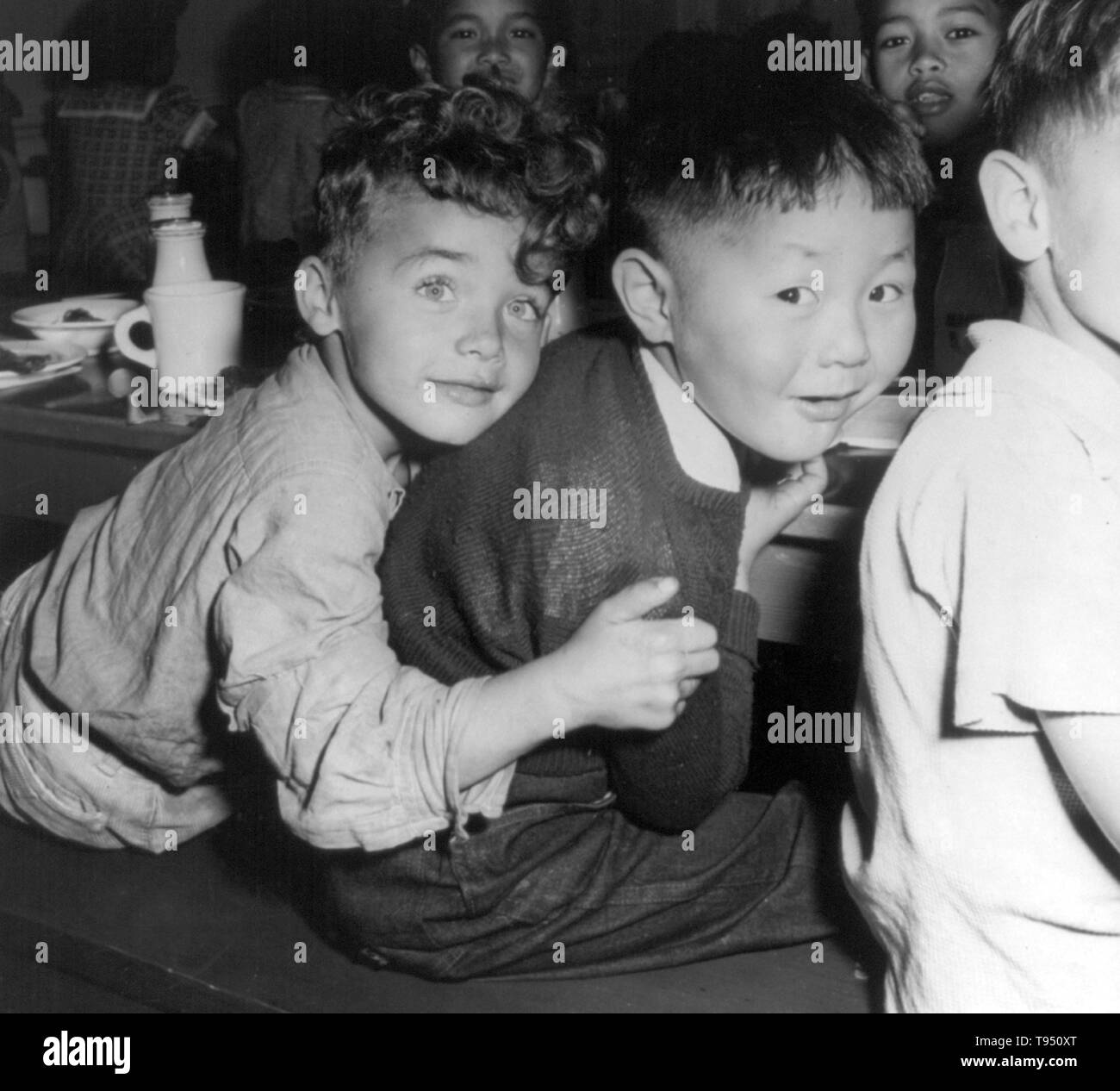 "Entitled: ""A lunch hour scene at the Weill public school in the international section. Many children of Japanese ancestry like the boy shown here with his chum, were evacuated with their parents from this neighborhood."" The internment of Japanese-Americans during WWII was the forced relocation and incarceration in camps of 110,000-120,000 people of Japanese ancestry ordered by President Roosevelt shortly after Japan's attack on Pearl Harbor. Stock Photo"