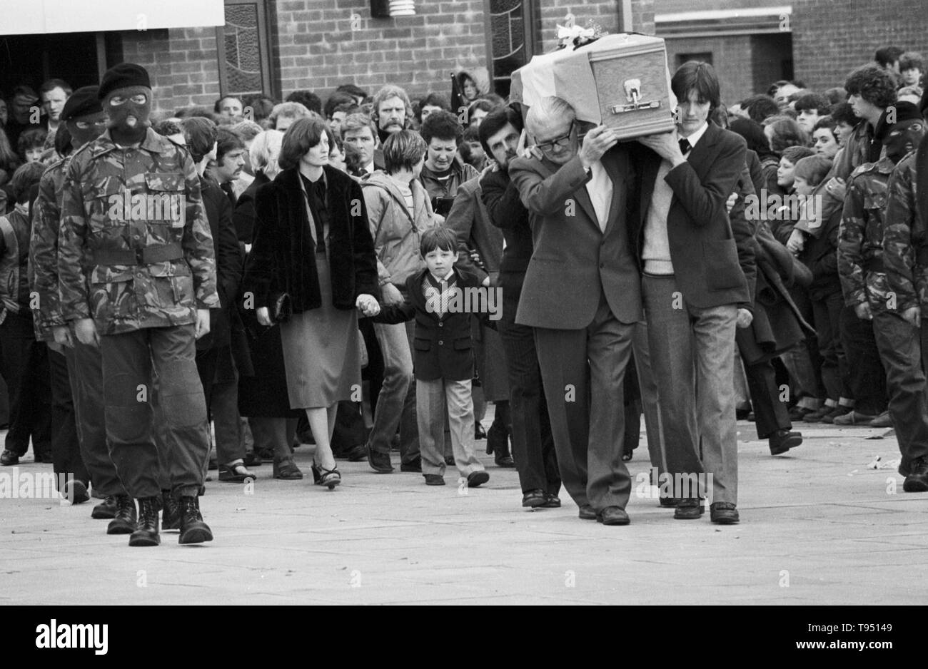 The coffin of Bobby Sands, MP is carried by his father (left, wearing glasses), his brother (r) and Owen Carron (moustache), his election agent, from St Luke's Church on the Twinbrook Estate, Belfast. the coffin is follow by Bobby Sands's sister, Marcella, who is holding the hand of Sands's son Gerald, and other members of the family en route to the burial in Milltown cemetery. - Stock Image