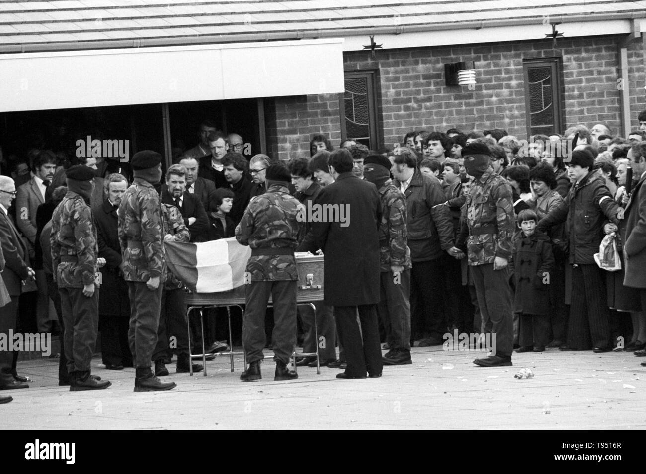 Masked and uniformed Provisionals drape the coffin of Bobby Sands, MP with the Irish tricolour, before moving off from St Luke's Church on the  Twinbrook Estate, Belfast, for the burial at Milltown cemetery. - Stock Image