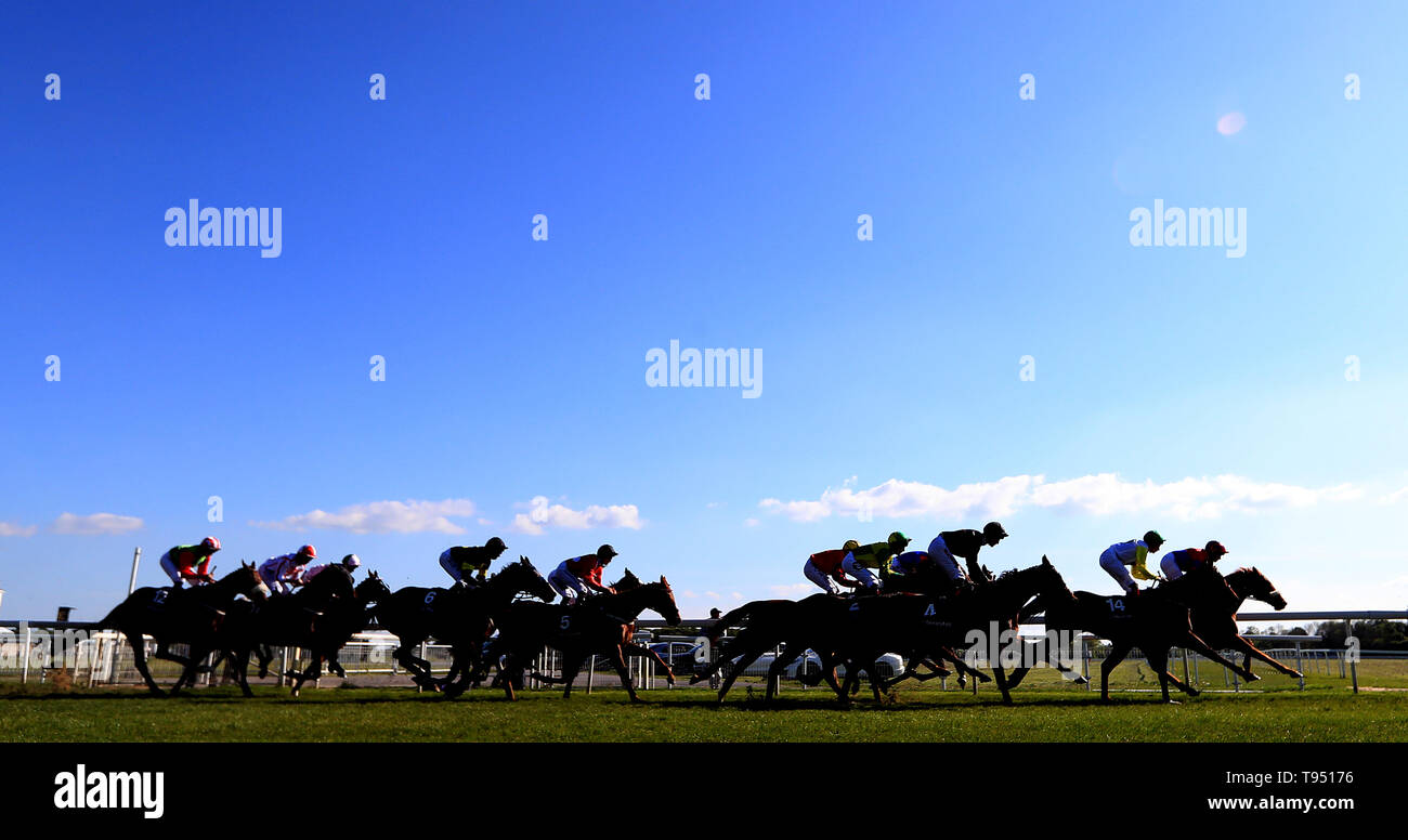 Runners and Riders round the first bend during The Investec Wealth Stakes during day two of the Dante Festival at York Racecourse. - Stock Image