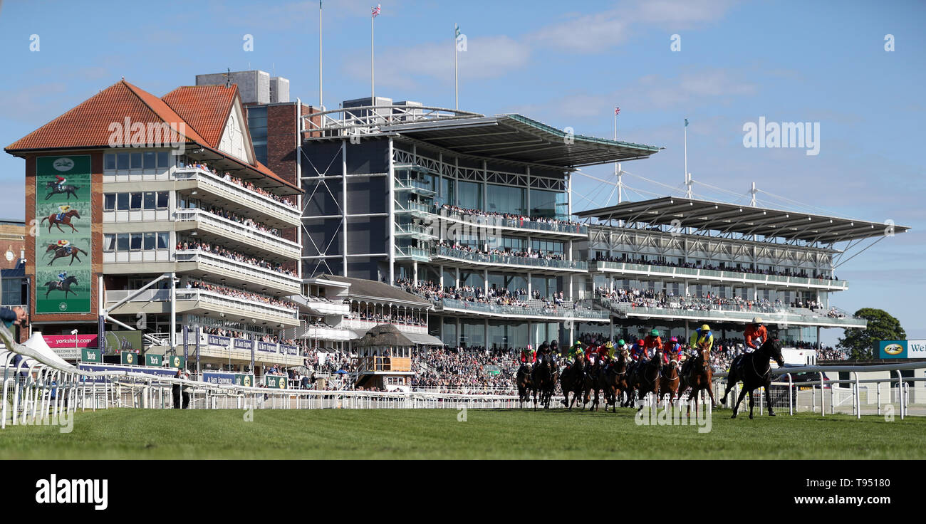 Runners and Riders round the first bend during The Investec Wealth Stakes during day two of the Dante Festival at York Racecourse. Stock Photo