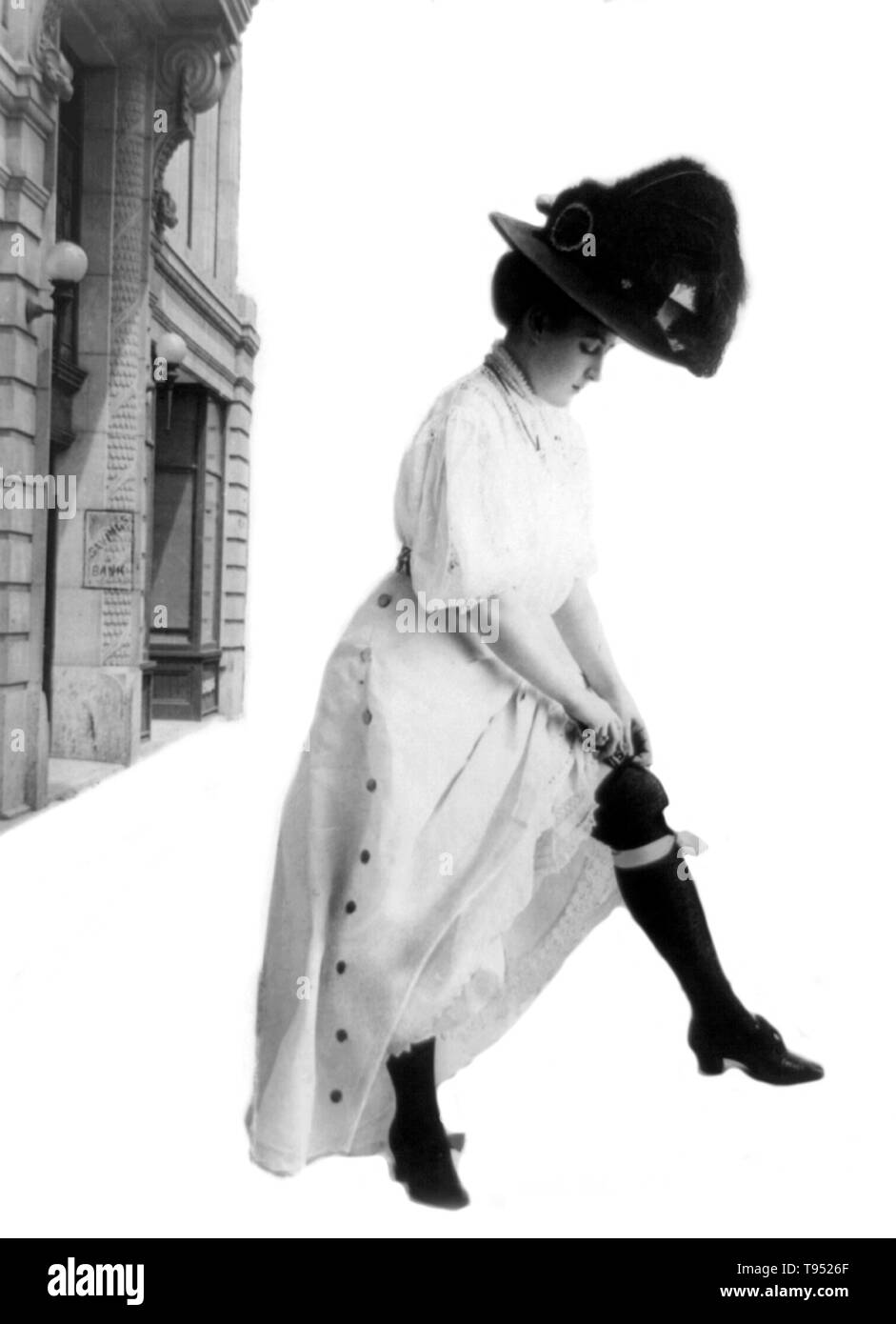 Entitled: 'Bank deposit' woman standing outside savings bank; wearing long dress and long feathered hat; she raises her skirt to insert $5 bill inside her gartered stocking. Photographed by Consolidated Art Company, 1908. - Stock Image