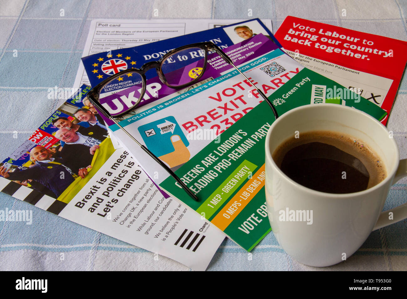 Mug of black coffee and glasses on top of European Parliament Election leaflets - Stock Image