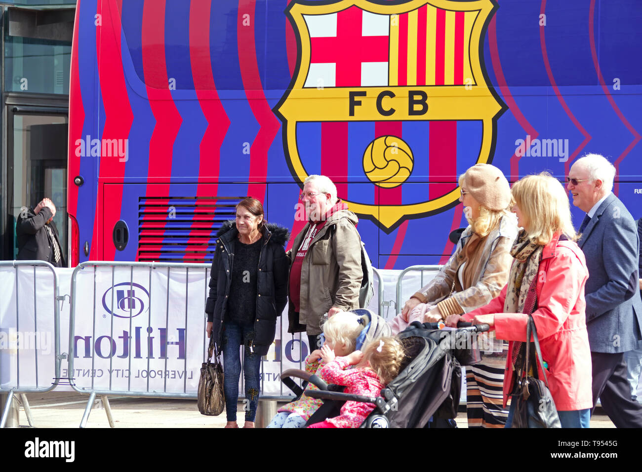 People pose for photographs in front of the FC Barcelona team coach in front of the Hilton Hotel Liverpool UK - Stock Image