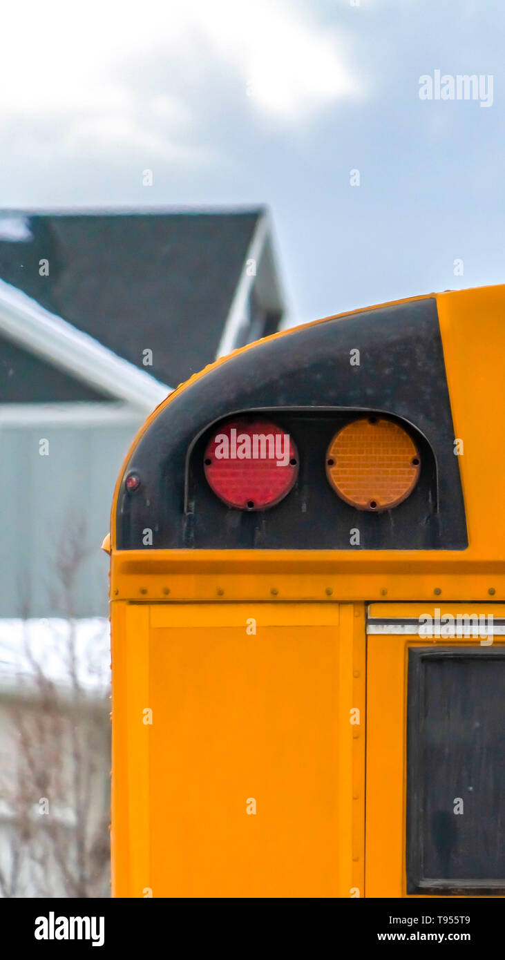 Vertical Close up of the rear of a school bus with a window and several signal lights - Stock Image