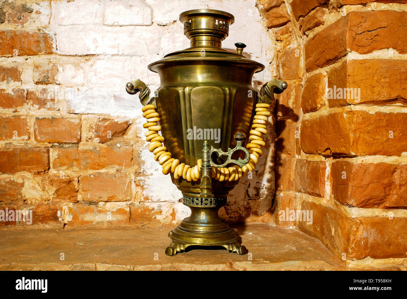 Ancient copper samovar stands in the form of decorations with lamb products on the background of the wall of the Russian red brick oven. Background, r - Stock Image