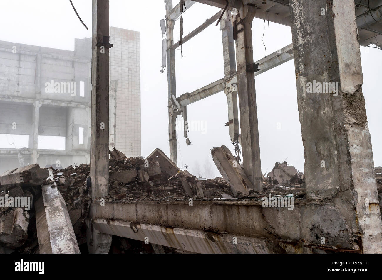 The destroyed big concrete building in a foggy haze. The remains of the frame of gray concrete piles and debris of the building structure. Background. - Stock Image