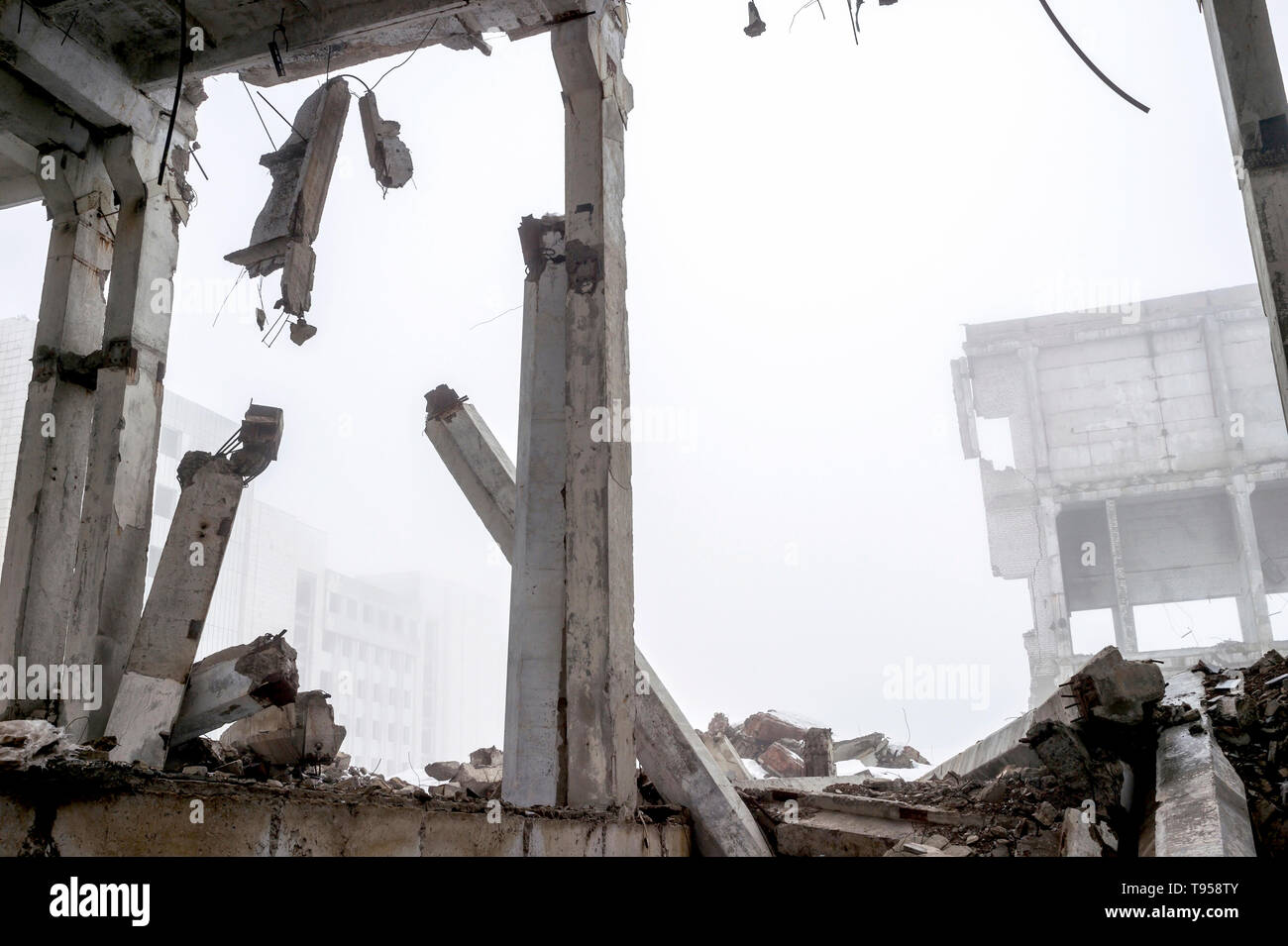 The destroyed big concrete building in a foggy haze. The remains of the frame of gray concrete piles and debris of the building structure. Background. Stock Photo