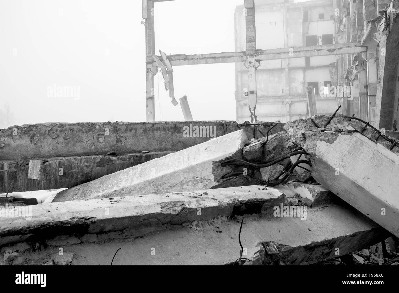 The destroyed big concrete building in a foggy haze. The frame of the building structure with huge piles lying in the foreground. Background. Black an - Stock Image