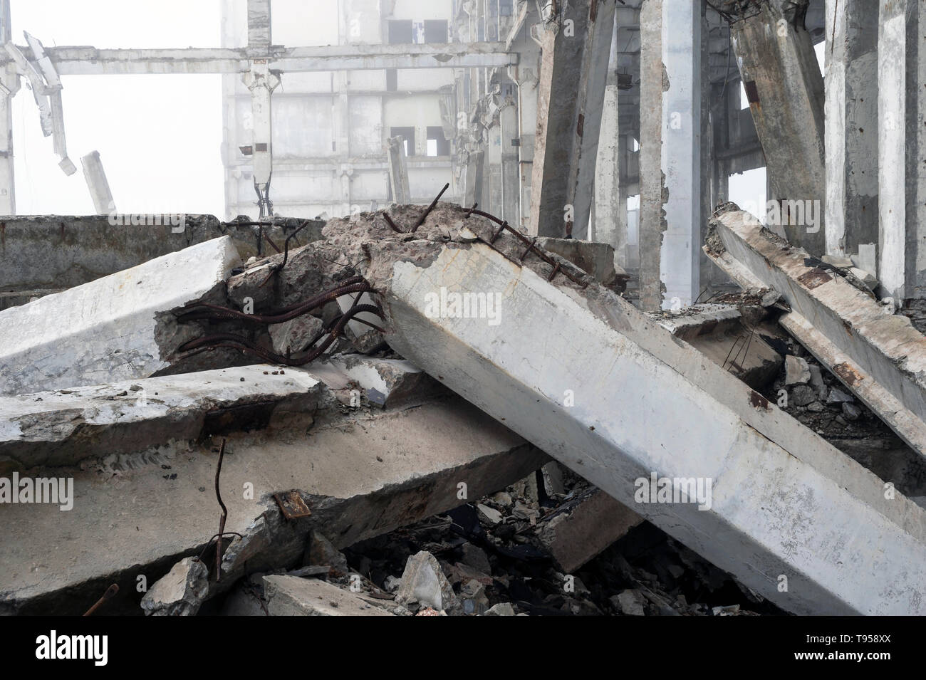 The destroyed big concrete building in a foggy haze. The frame of the building structure with huge piles lying in the foreground. Background. - Stock Image