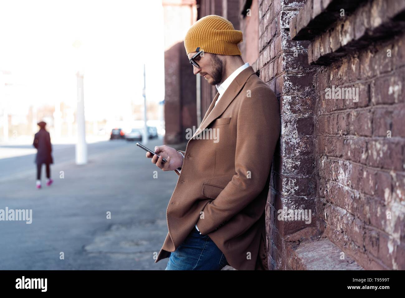 handsome hipster modern man using smart phone in the city - Stock Image