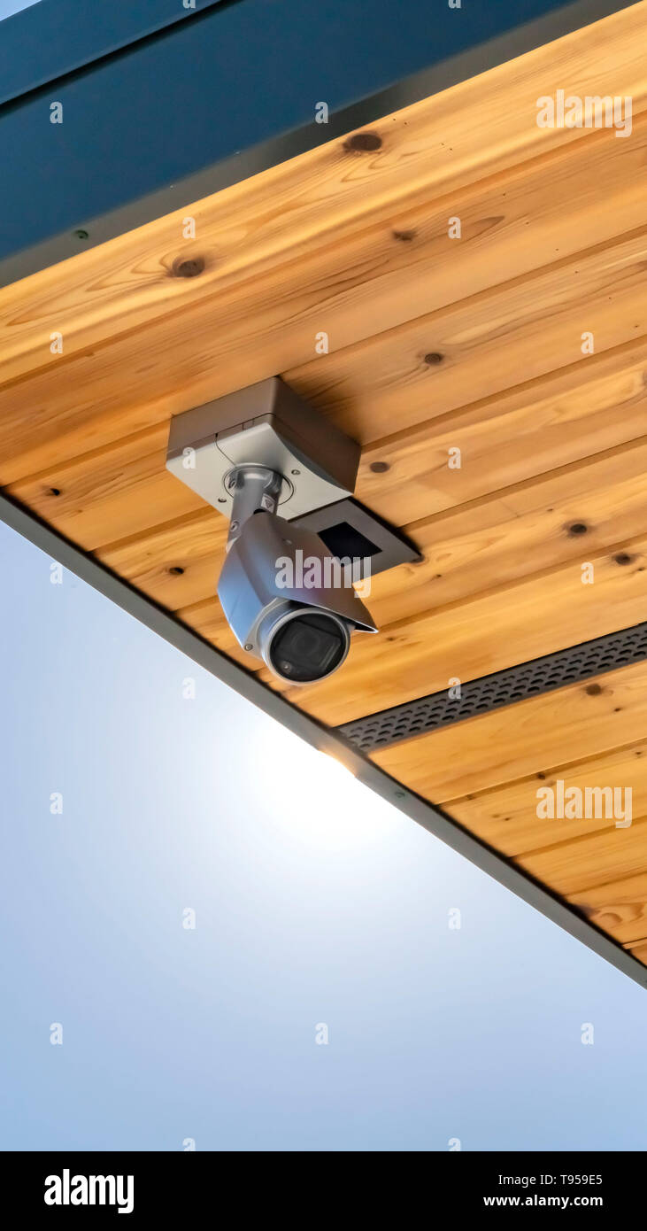 Clear Vertical Home with security camera installed on the wooden underside of its roof - Stock Image