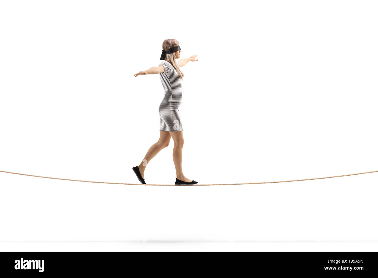 Full length profile shot of a woman walking on a rope and wearing blindfold isolated on white background - Stock Image
