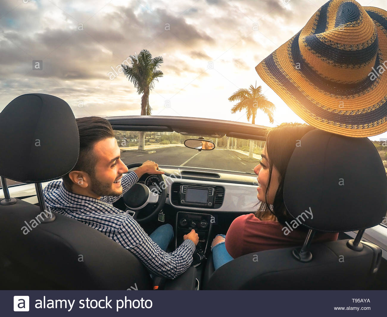 Welp Trendy rich couple having fun driving convertible car at sunset GP-71