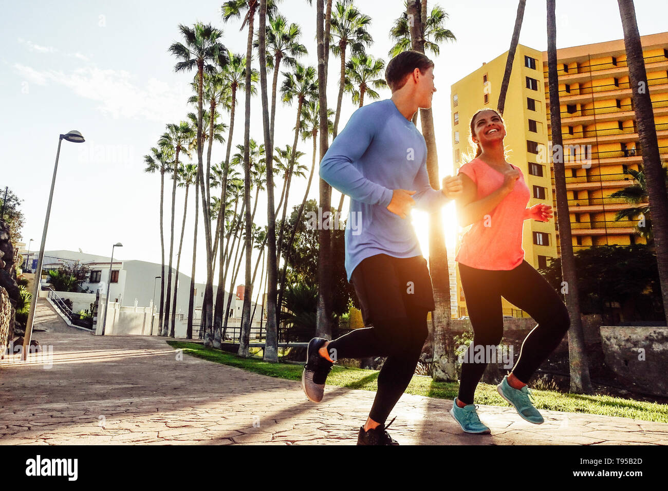 Healthy young couple jogging together at sunset time outdoor - Happy sportive people running in the city Stock Photo
