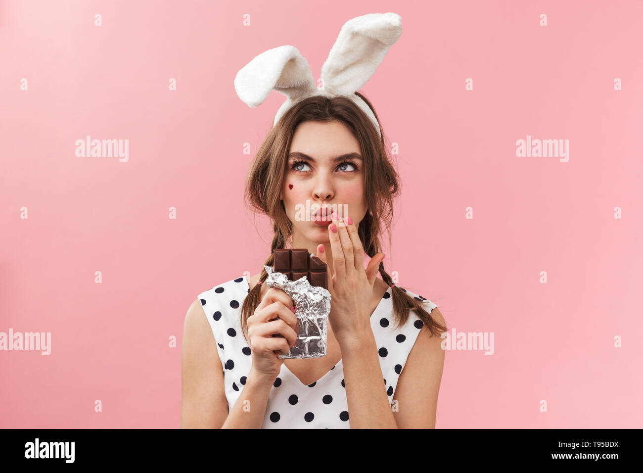 c3a6a94bbda2 Portrait of a pretty lovely girl wearing bunny ears standing isolated over  pink background, eating