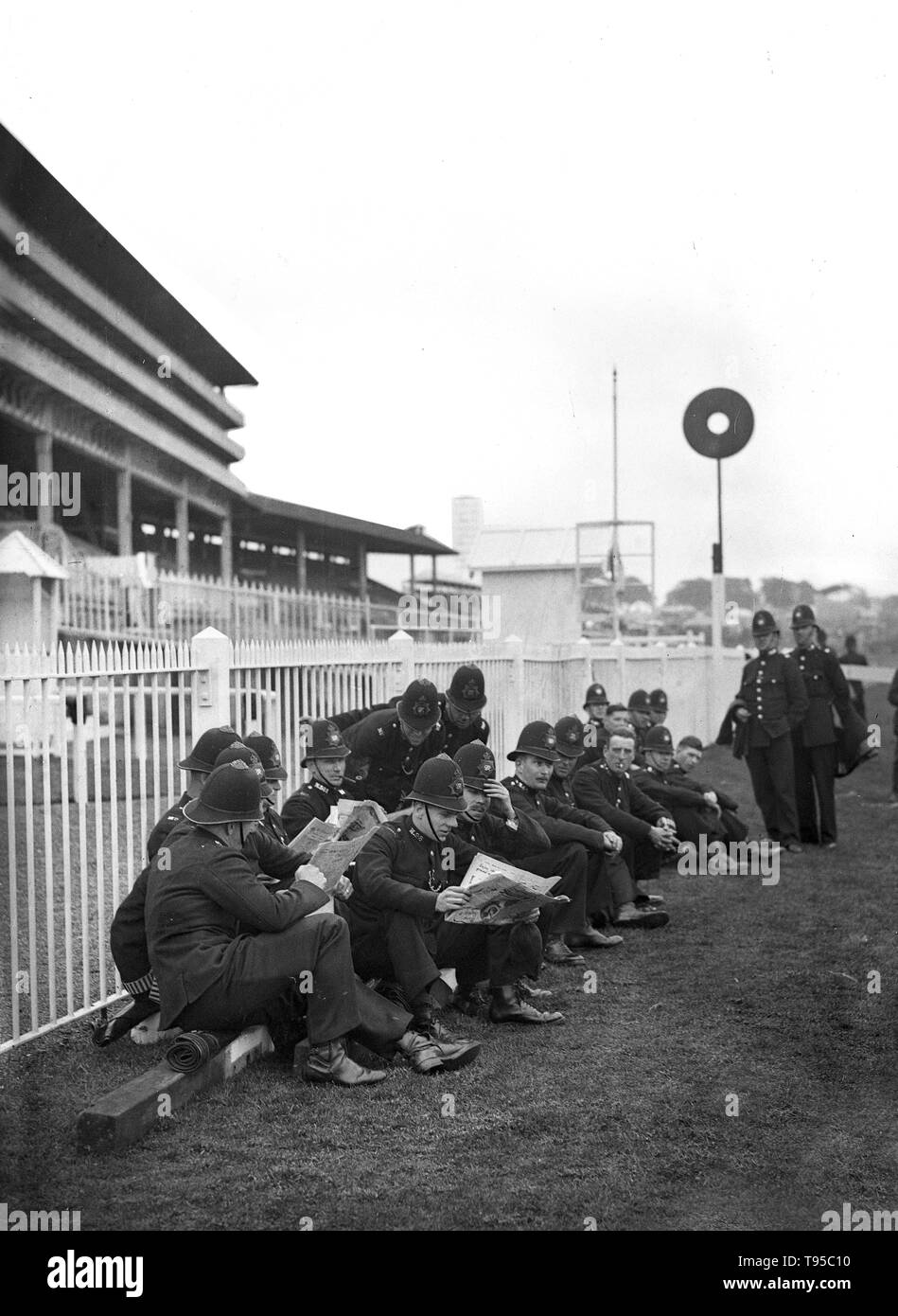 British policemen checking for racing tips at the Epsom Derby races in June 1932 - Stock Image