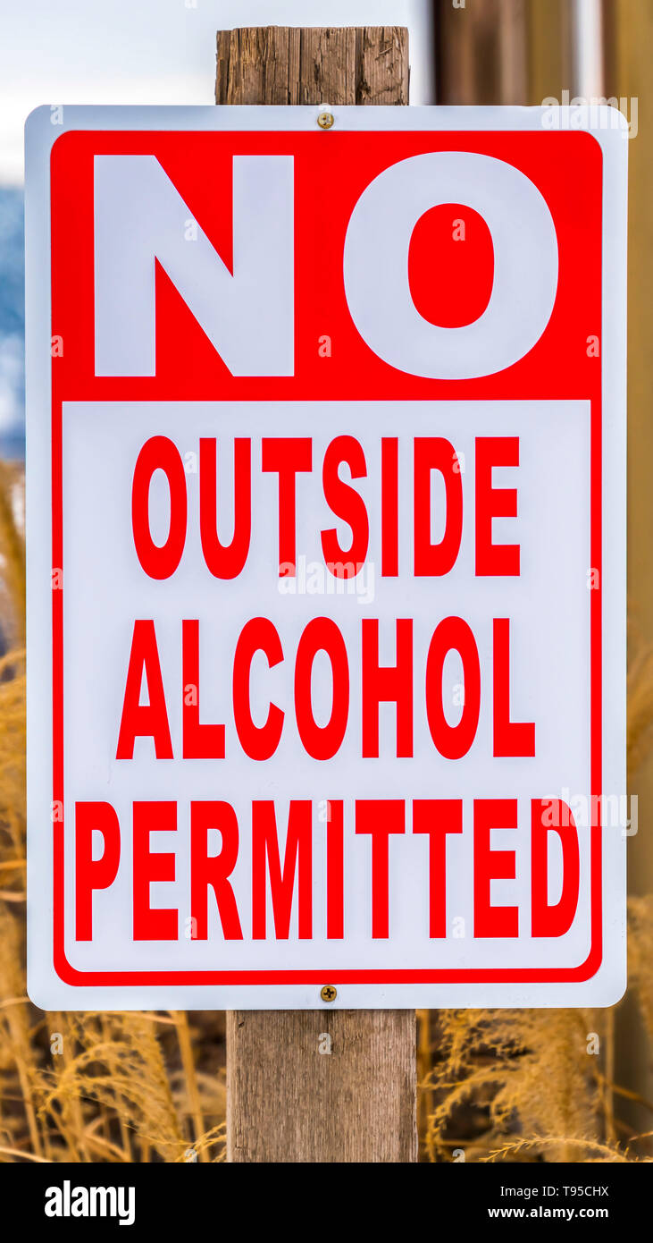 Vertical Close up view of a sign post that reads No Outside Alcohol Permitted - Stock Image