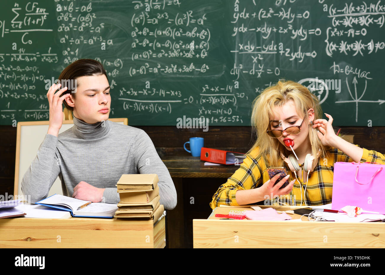 Tutors fill different role than teachers and parents. Old books on a round wooden table. Confident student studying for exam at desk with laptop - Stock Image