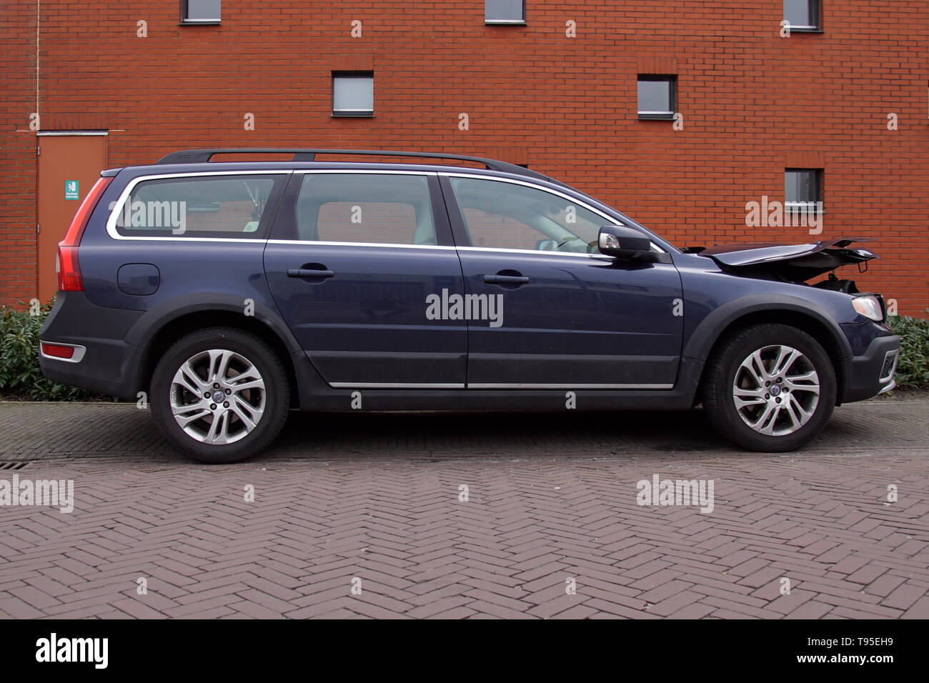 Naarden, the Netherlands - March 23, 2018: Volvo v70 with accident damage parked by the side of the road. Nobody in the vehicle. - Stock Image