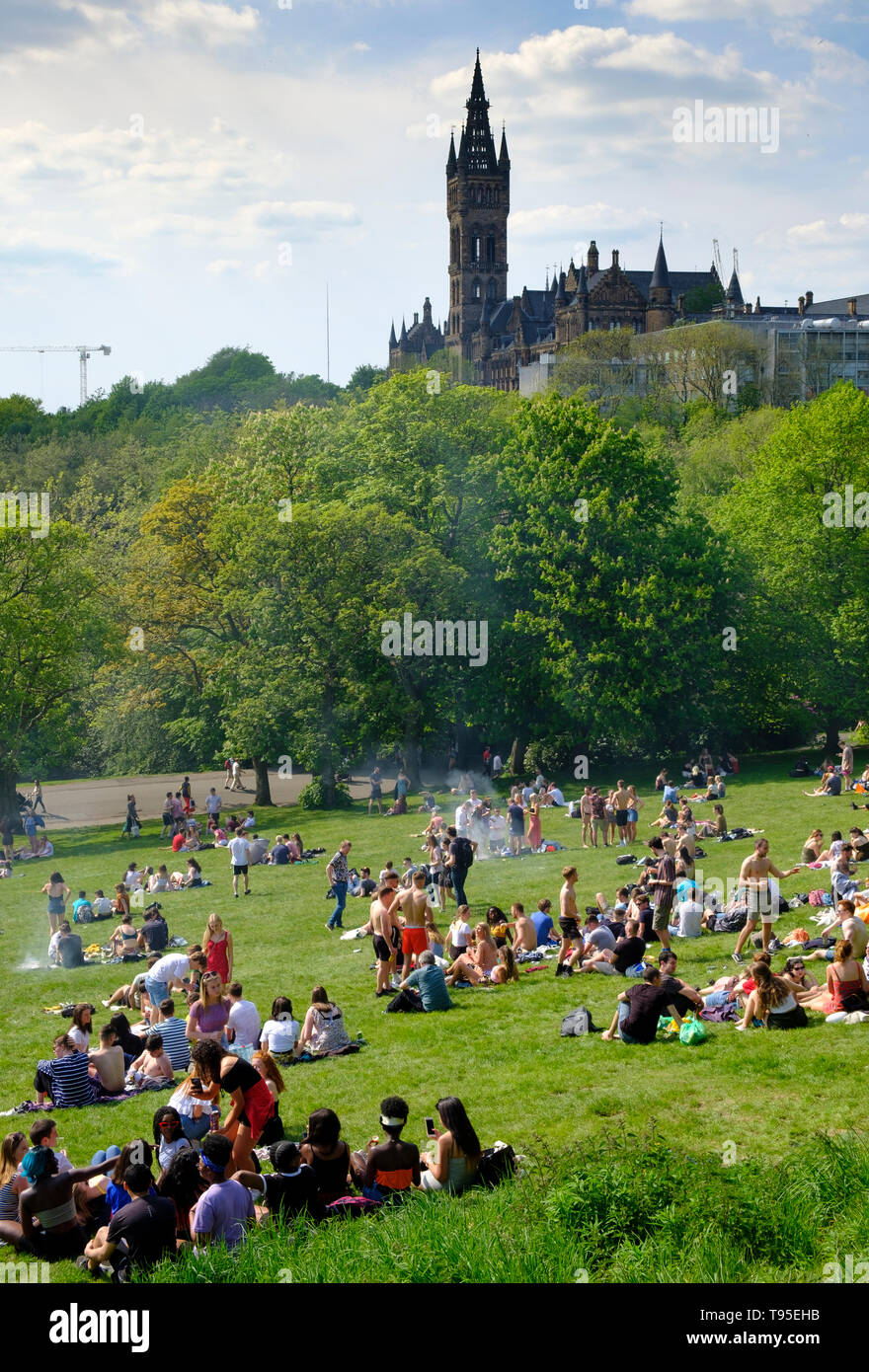 Hot weather and people in Glasgow Kelvingrove Park with Glasgow University to rear in Glasgow West End, Scotland, UK - Stock Image
