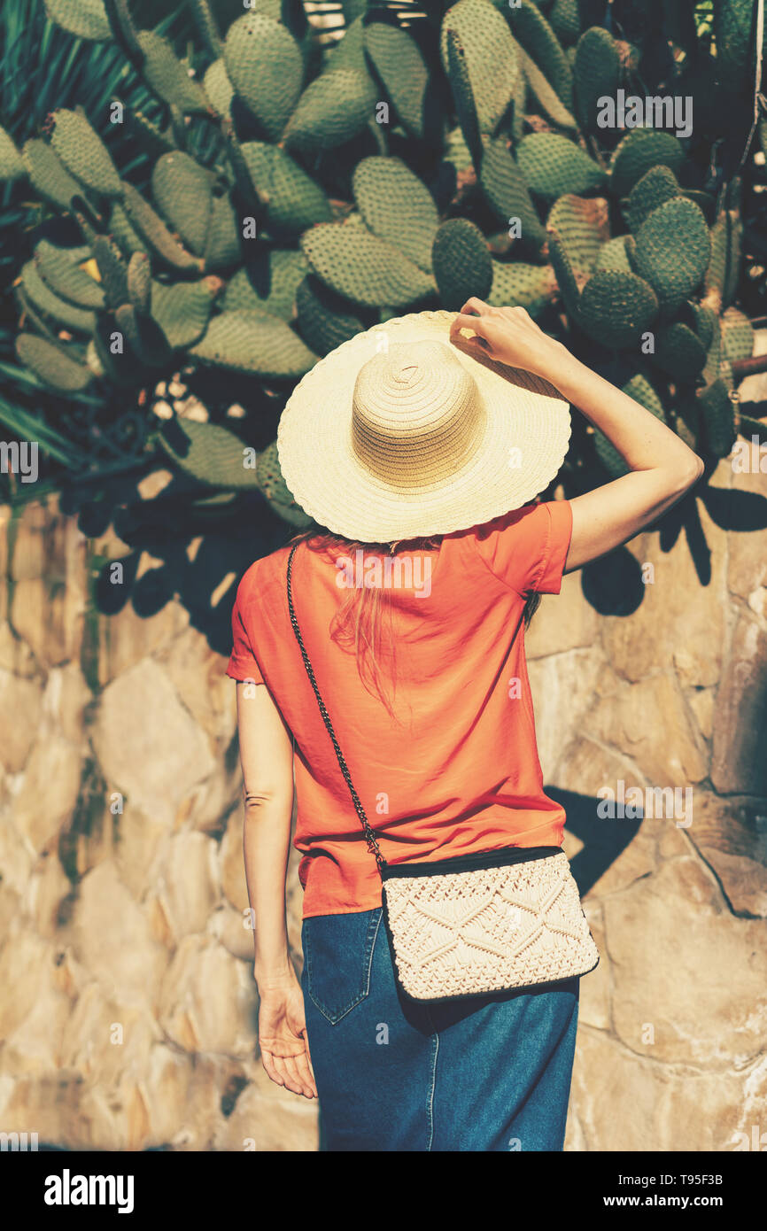 View from the back of a woman in a straw hat and with a bag on a chain looking at cacti. Summer concept, vertical format - Stock Image
