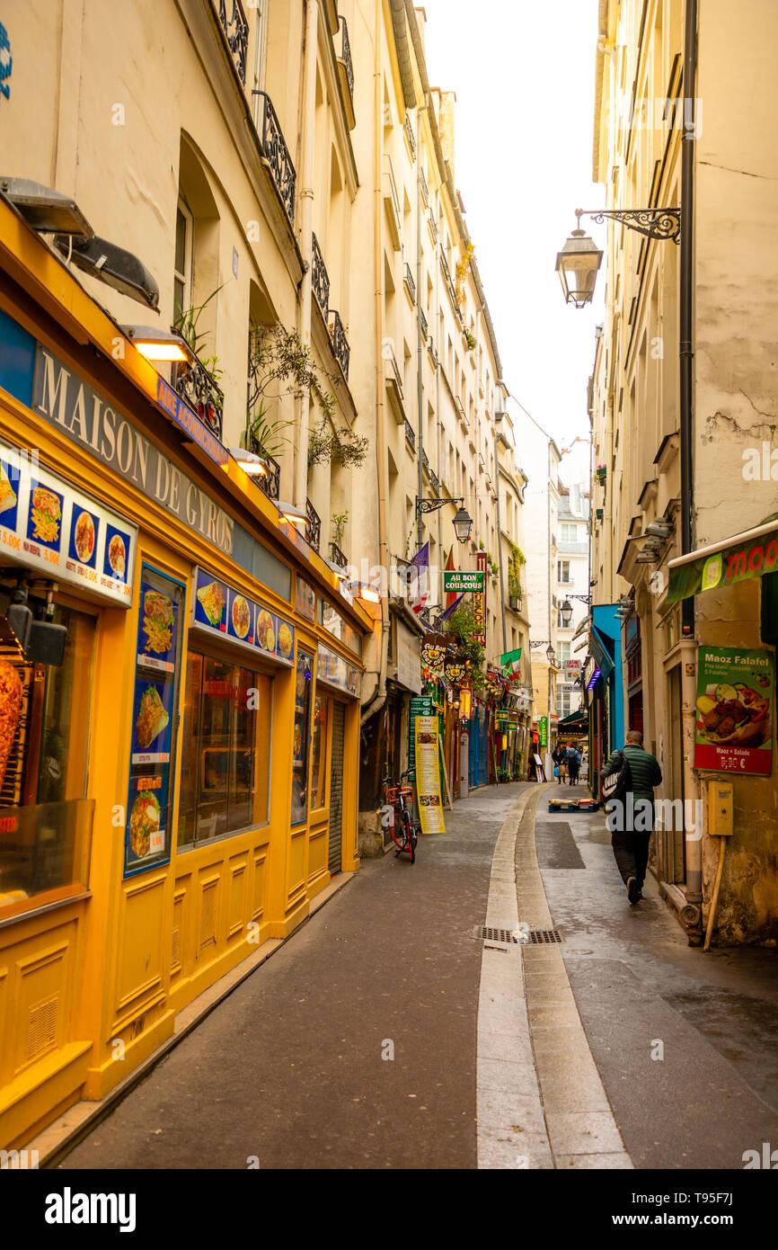 Paris, France - 24.04.2019: Latin Quarter. Narrow street of Paris among old traditional parisian houses and cafe in Paris, France - Stock Image