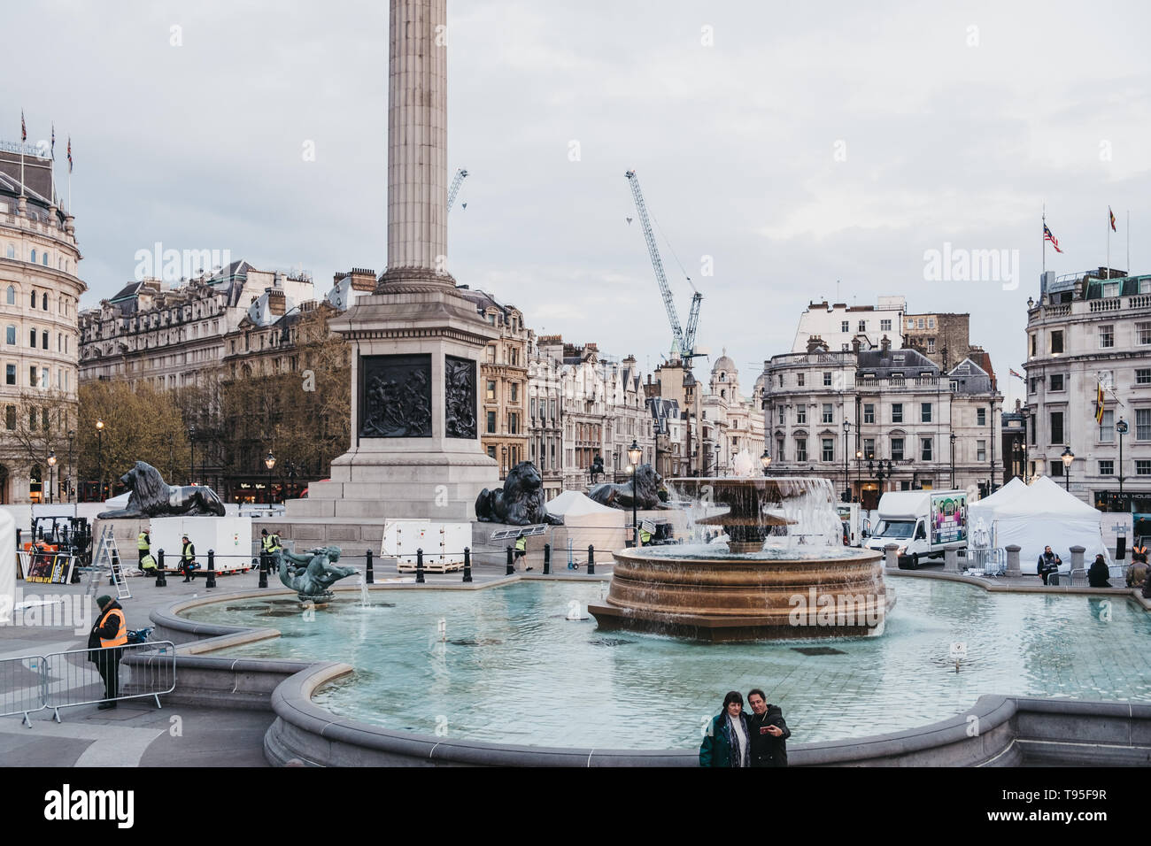 London, UK - April 14, 2019: People talking photos in front of fountains on Trafalgar Square, a public square in Charing Cross area of London that fea - Stock Image