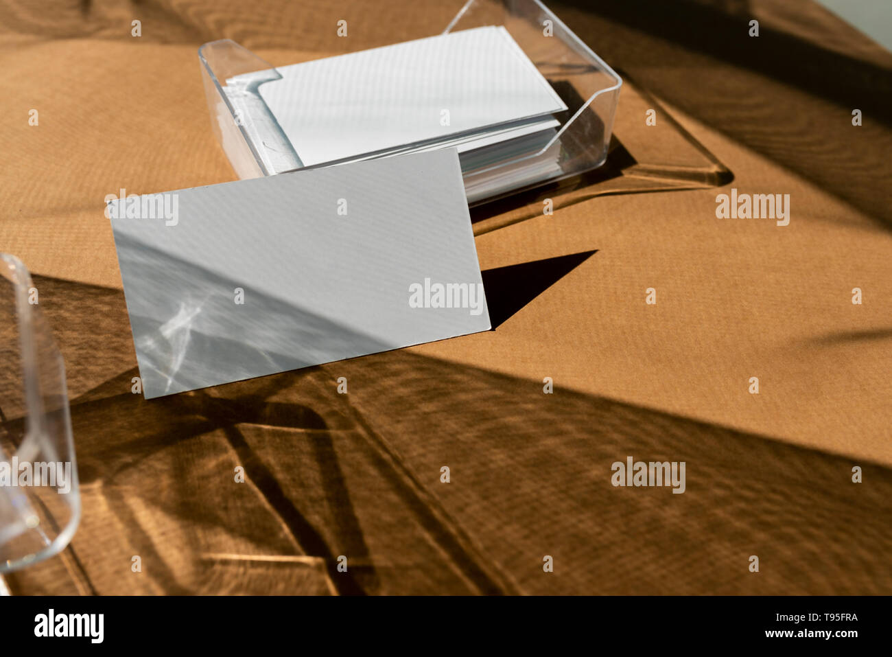 Blank business cards on transparent box, and direct light forming geometric shadows - Stock Image