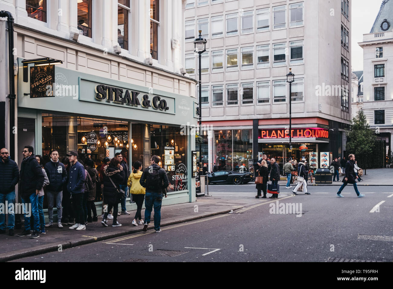 London, UK - April 14, 2019: People walking past Steak & Co restaurant on the corner of Haymarket, a street in the St. James's area of London, famous  - Stock Image