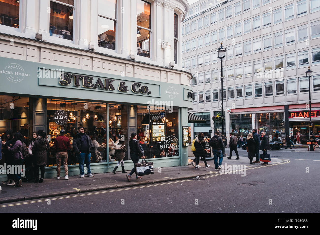 London, UK - April 14, 2019: People walking past Steak & Co restaurant on the corner of Haymarket, a street in the St. James's area of London, famous  Stock Photo