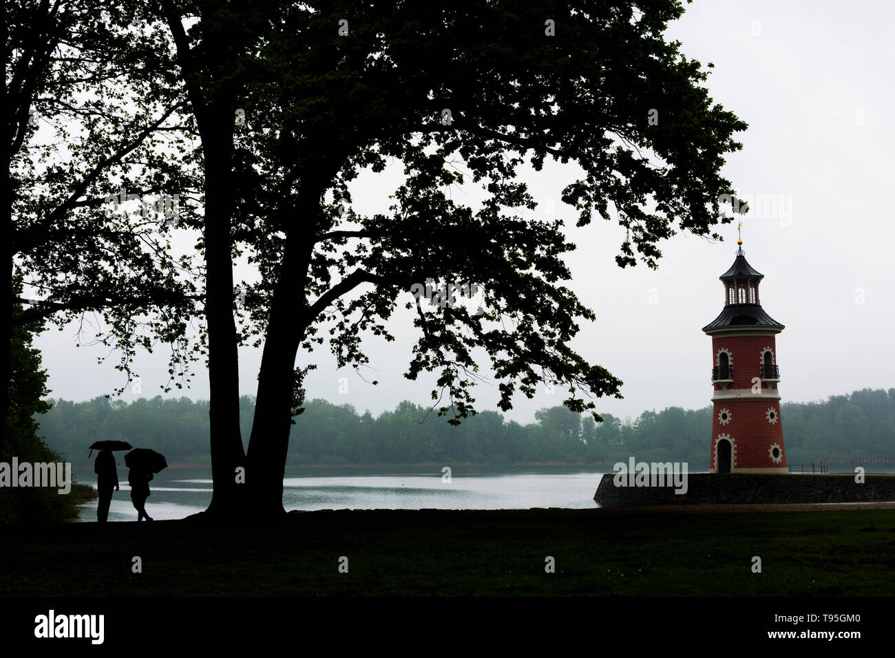 Moritzburg: Lighthouse with jetty at pond Großteich, rain, people with umbrella in , Sachsen, Saxony, Germany Stock Photo
