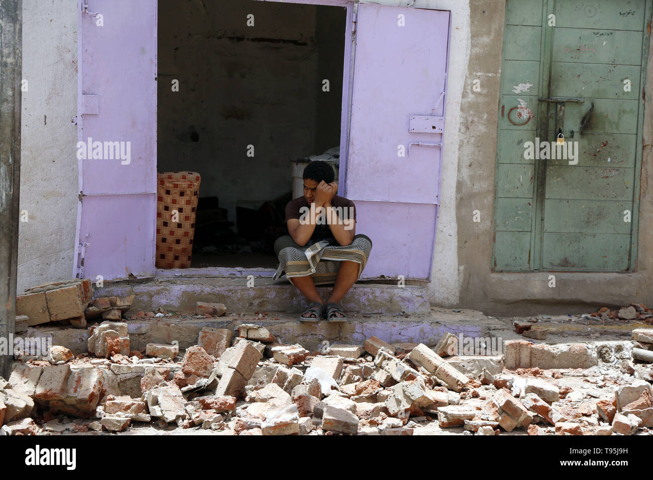 Sanaa, Yemen. 16th May 2019. A man sits on rubble of a house after an airstrike hit by the Saudi Arabia-led coalition in Sanaa, capital of Yemen, May 16, 2019. The Saudi Arabia-led coalition launched airstrikes on Houthi rebels' targets in the Yemeni capital Sanaa on Thursday morning, causing civilian casualties and damages, authorities and local residents said. Credit: Xinhua/Alamy Live News - Stock Image