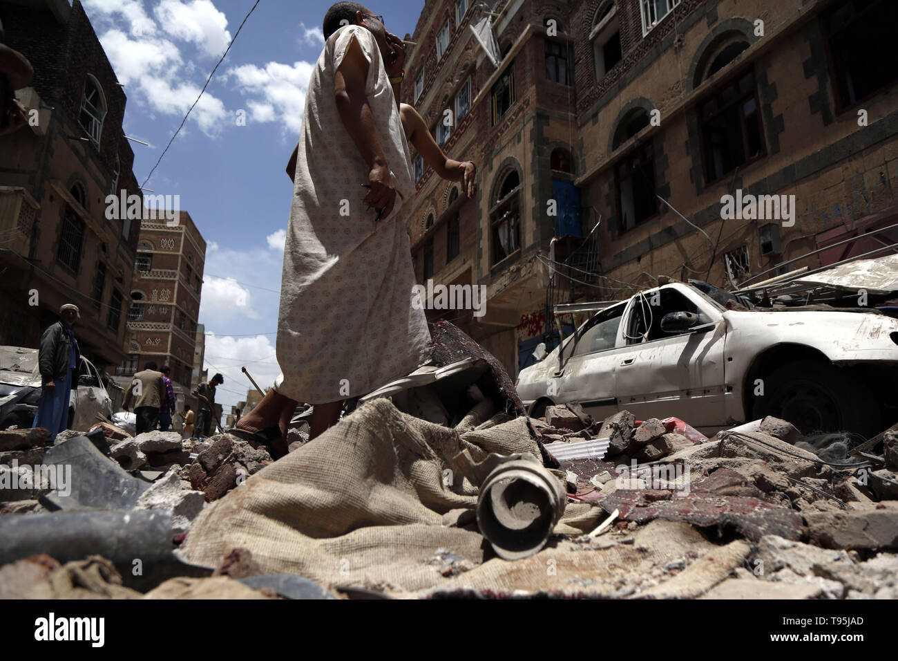 Sanaa, Yemen. 16th May 2019. People inspect damaged houses after an airstrike hit by the Saudi Arabia-led coalition in Sanaa, capital of Yemen, May 16, 2019. The Saudi Arabia-led coalition launched airstrikes on Houthi rebels' targets in the Yemeni capital Sanaa on Thursday morning, causing civilian casualties and damages, authorities and local residents said. Credit: Xinhua/Alamy Live News - Stock Image