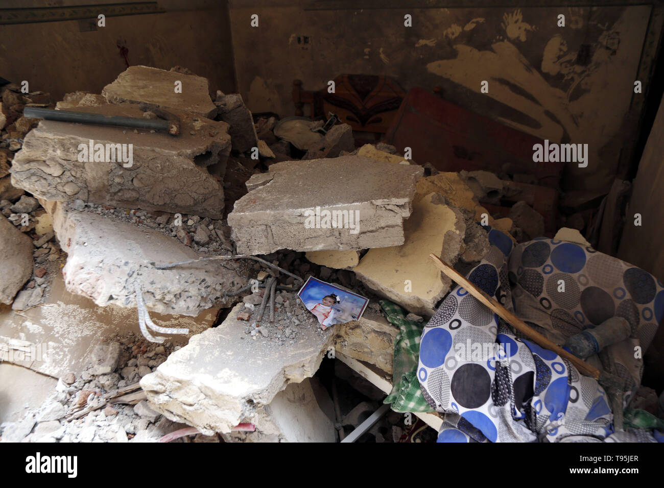 Sanaa, Yemen. 16th May 2019. A picture of a child is seen among rubble of a damaged house after an airstrike hit by the Saudi Arabia-led coalition in Sanaa, capital of Yemen, May 16, 2019. The Saudi Arabia-led coalition launched airstrikes on Houthi rebels' targets in the Yemeni capital Sanaa on Thursday morning, causing civilian casualties and damages, authorities and local residents said. At least six family members were killed when a coalition airstrike hit a house in the center of Sanaa, the rebel-controlled Health Ministry said in a statement. Credit: Xinhua/Alamy Live News - Stock Image