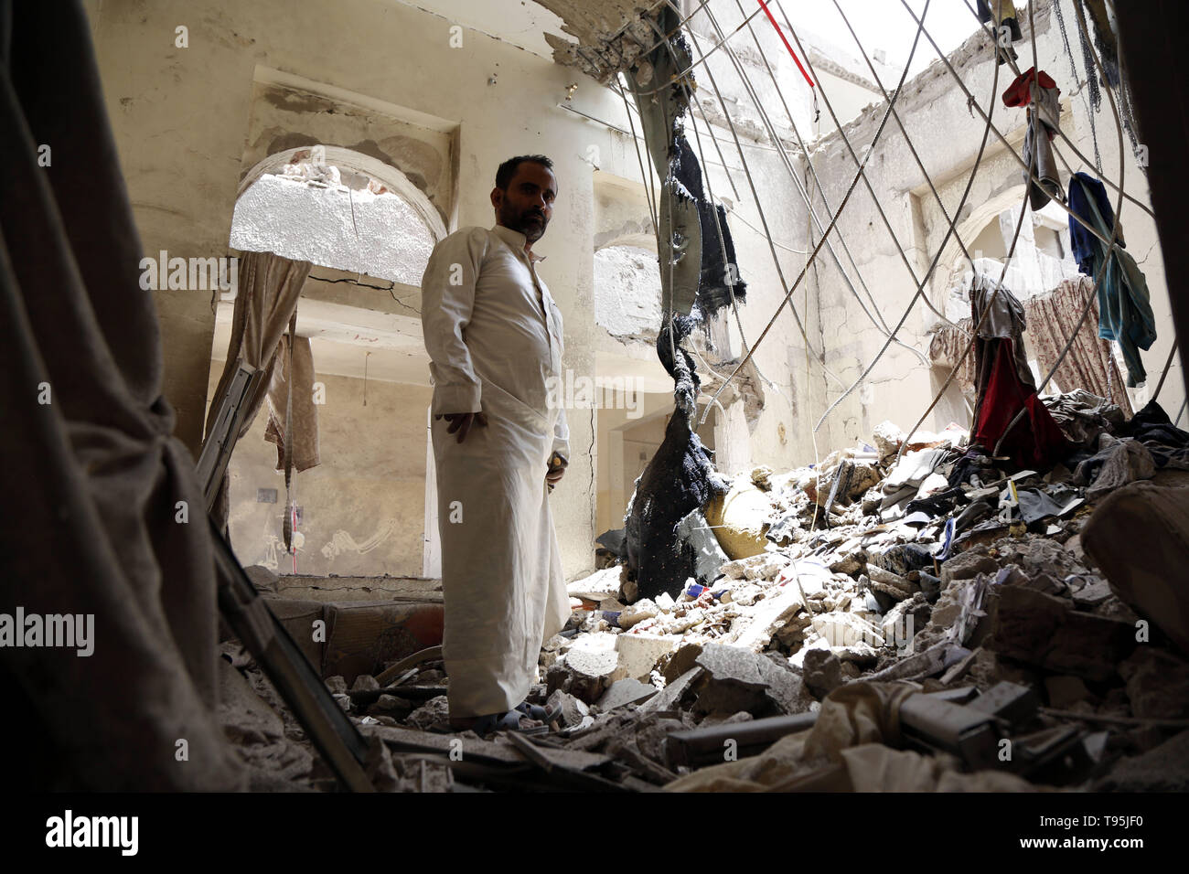 Sanaa, Yemen. 16th May 2019. A man inspects a damaged house after an airstrike hit by the Saudi Arabia-led coalition in Sanaa, Yemen, May 16, 2019. The Saudi Arabia-led coalition launched airstrikes on Houthi rebels' targets in the Yemeni capital Sanaa on Thursday morning, causing civilian casualties and damages, authorities and local residents said. Credit: Xinhua/Alamy Live News - Stock Image
