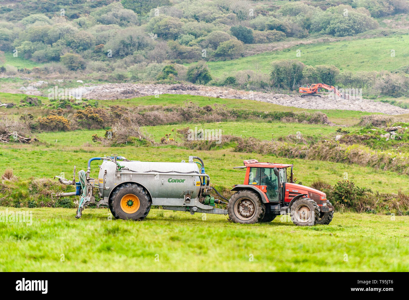 Ballydehob, West Cork, Ireland. 16th May, 2019. A farmer spreads slurry using a trailing shoe slurry spreader on a very overcast and dull day.  There will be scattered showers for the rest of the day with top temps of 14 to 18°C. Credit: Andy Gibson/Alamy Live News. - Stock Image
