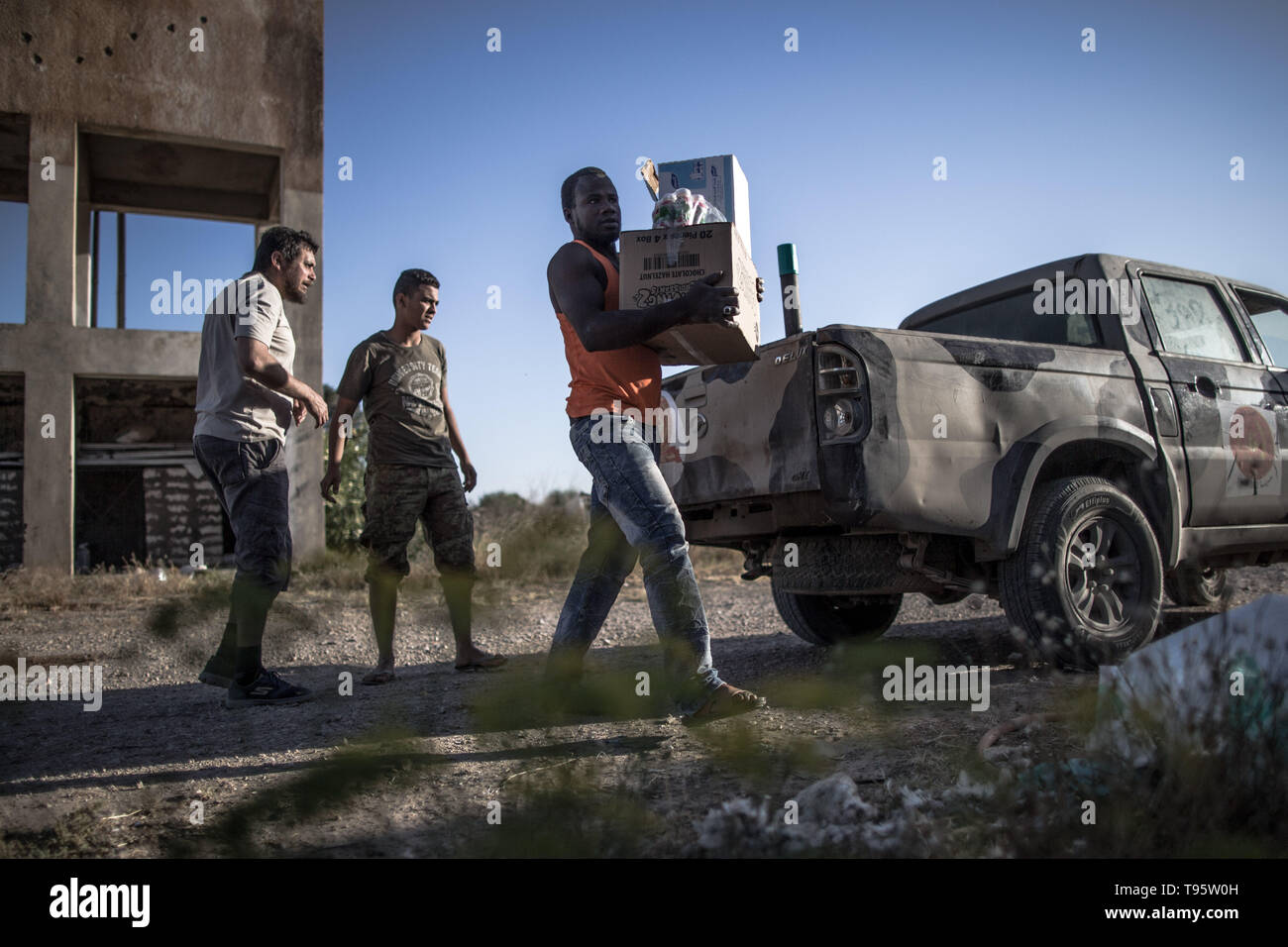 Tripoli, Libya. 16th May, 2019. Fighters from UN-backed government forces distribute food and aid to civilian workers trapped in abandoned farms in the fighting areas near Al-Sawani frontline in Tripoli, Libya, on May 16, 2019. At least six civilians were reported killed and five more injured in an apparent airstrike in populated areas of the Libyan capital of Tripoli, Stephane Dujarric, spokesman for UN Secretary-General Antonio Guterres, said on Thursday. Credit: Amru Salahuddien/Xinhua/Alamy Live News - Stock Image